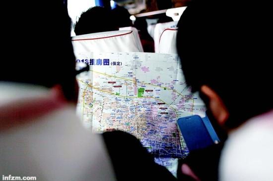 保定东站,看房团的大巴即将发车,当天早上坐高铁赶来保定看房的人在座位上研究各楼盘的介绍资料。 (南方周末记者 张涛/图)